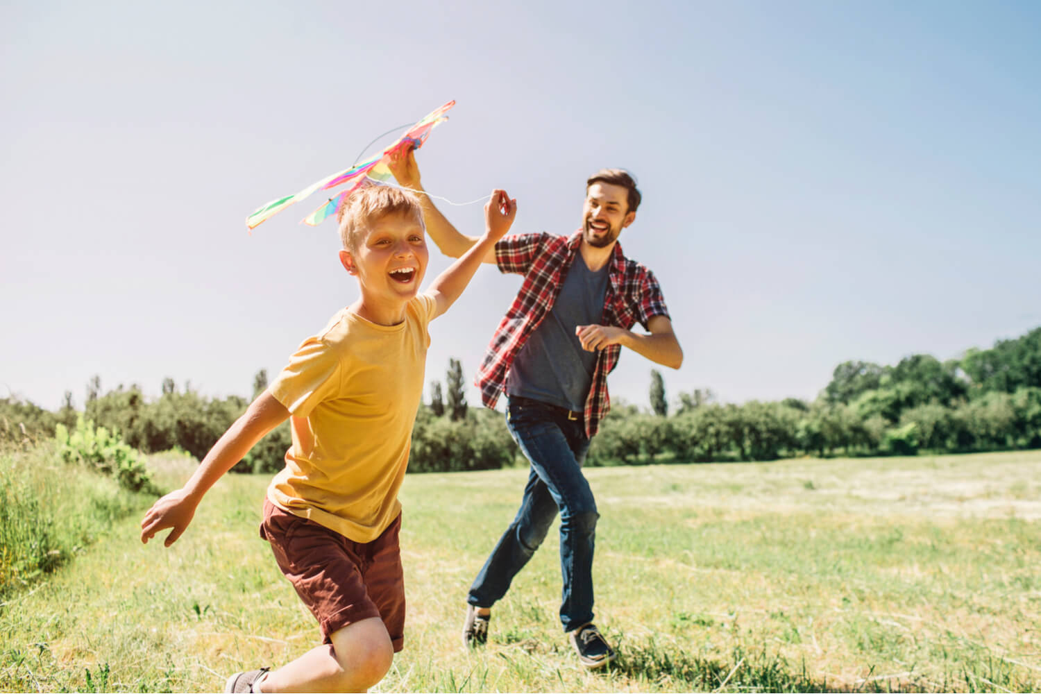 A father and son galivanting with kites through a field during their spring break in Wisconsin Dells.