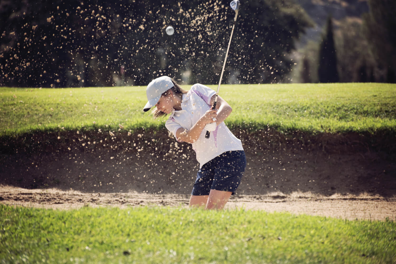 A female golfer chips out of the sand trap at a Wisconsin Dells golf course.